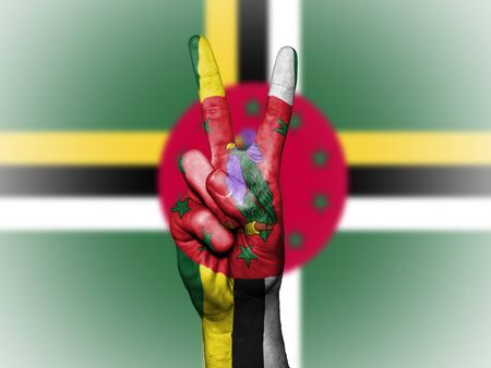 Hand showing the international symbol for peace, decorated in the national colors of Dominica