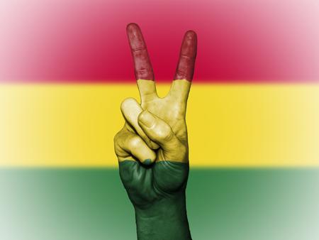 Mano que muestra el símbolo internacional de la paz, decorado con los colores nacionales de Bolivia