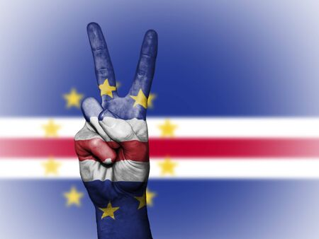 Hand showing the international symbol for peace, decorated in the national colors of Cabo Verde Stock Photo
