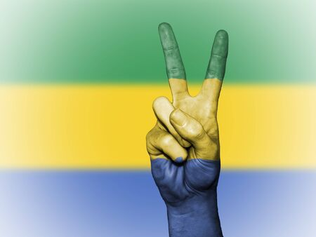 Hand showing the international symbol for peace, decorated in the national colors of Gabon