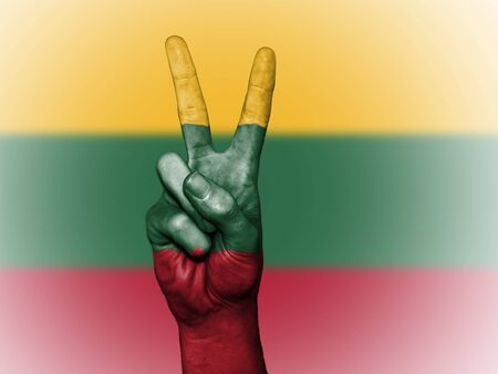 Hand showing the international symbol for peace, decorated in the national colors of Lithuania Stock Photo
