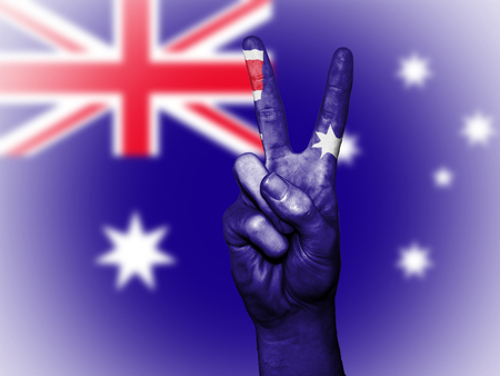 Hand showing the international symbol for peace, decorated in the national colors of Australia Stock Photo