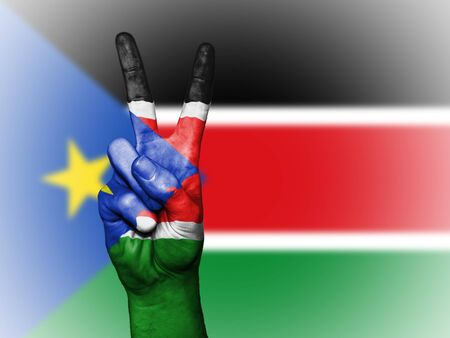 Hand showing the international symbol for peace, decorated in the national colors of South Sudan Stock Photo