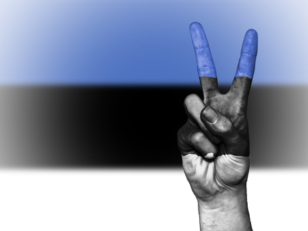 Hand showing the international symbol for peace, decorated in the national colors of Estonia