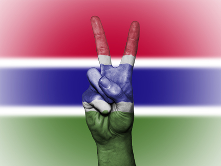 Hand showing the international symbol for peace, decorated in the national colors of The Gambia Stock Photo