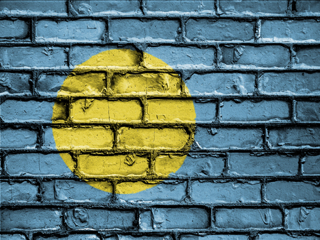 royalty free photo: National Flag of Palau on a Brick Wall Stock Photo