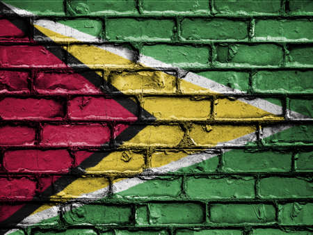 royalty free photo: National Flag of Guyana on a Brick Wall