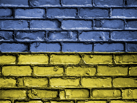 royalty free photo: National Flag of Ukraine on a Brick Wall