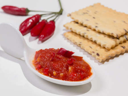 Hot spicy chili pepper sauce on white background