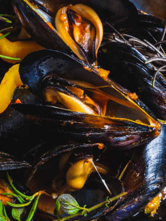 Delicious mussels cooked with peppers in wok closeup