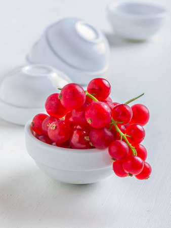 Fresh currants with bowls on white background
