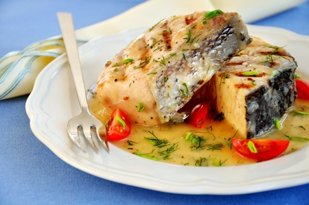 Grilled fish fillet on a white plate photo