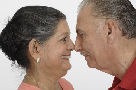 Old couple,old man and woman facing each other and touching noses and smiling