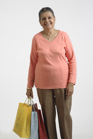 Old lady holding colourful shopping bags in her right hand