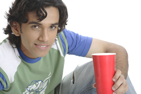 Teenage boy holding glass of soft drink and smiling Stock Photo