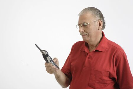Old man holding cordless phone and dialling Stock Photo