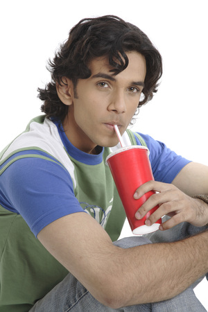 Teenage boy holding glass of soft drink and drinking with straw