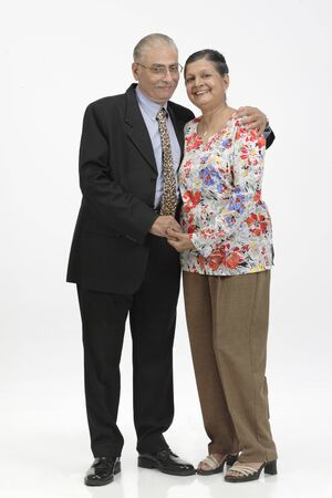 Old couple standing close to each other looking at camera and smiling