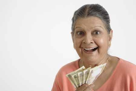 Old lady holding five notes of Rs.500 each in her hand and laughing