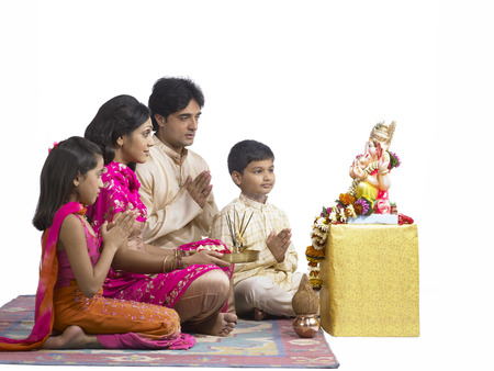South Asian Indian family with father mother son and daughter sitting praying to lord Ganesha