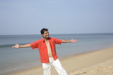 Südasiatischer indischer junger Mann, der auf Sand steht, verbreitete Hände gerade beide Seite des Körpers an der Küste, Shiroda, Dist. Sindhudurga, Maharashtra, Indien