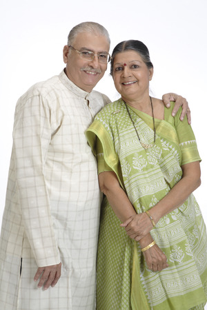 Old happy couple standing close to each other and smiling
