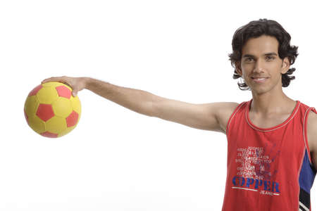 Teenage boy holding football in hand showing upside down