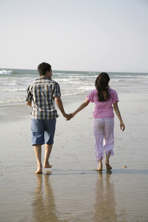 South Asian Indian young man and woman holding hands walking together on seashore,Shiroda,Dist. Sindhudurga,Maharashtra,India