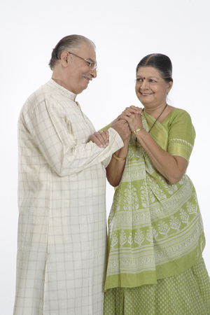 Old happy couple standing close to each other holding hand Stock Photo