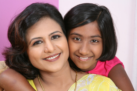 South Asian Indian young lady wearing yellow sari with her daughter