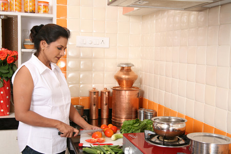South Asian Indian young lady wearing western clothes and working in the modern kitchen