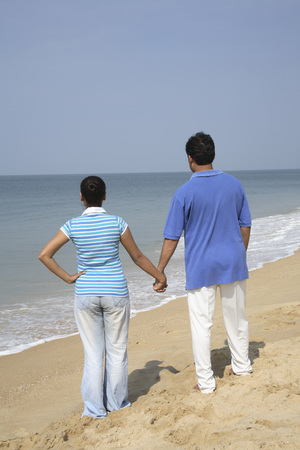 South Asian Indian young man and woman standing with holding hands looking at sea on seashore,Shiroda,Dist. Sindhudurga,Maharashtra,India