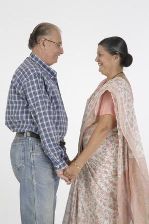 Old happy couple standing with holding hand facing each other and smiling Stock Photo