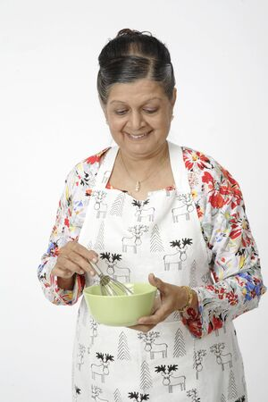 Old woman holding light green coloured bowl and egg beater or hand mixer