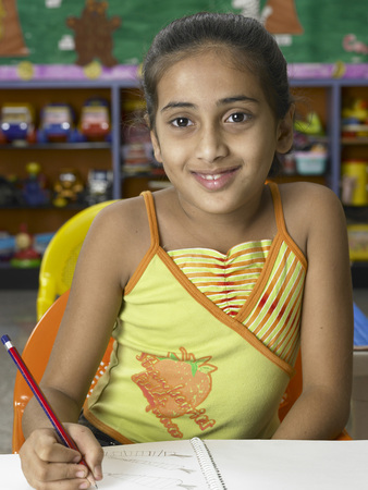 South Asian Indian girl with book and pencil studying in nursery school