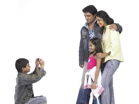 South Asian Indian family son taking picture of father mother and daughter