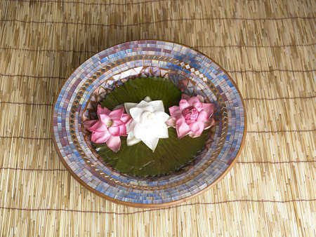 Two red and one white lotus flower kept in plate on the wooden mat