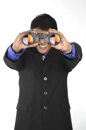 Executive holding binocular and looking through it