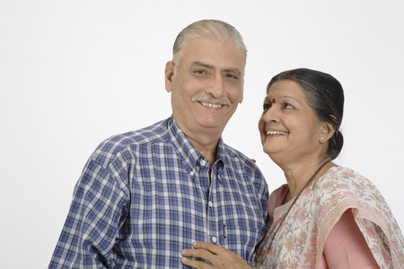 Old couple smiling,lady kept her right hand on shoulder and other on chest looking at man Stock Photo
