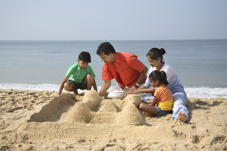 South Asian Indian parent and children making sand castle on seashore at Shiroda,Dist. Sindhudurga,Maharashtra,India Stock Photo