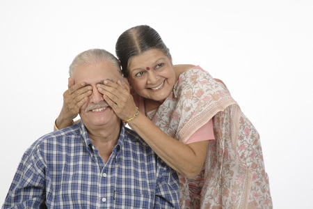 Old happy couple,lady standing behind man and closing both eyes