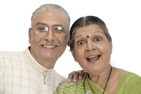 Old happy couple standing close to each other touch their heads and smiling Stock Photo