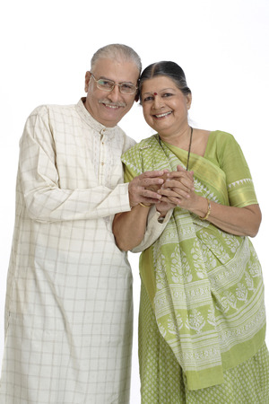 Old happy couple standing close to each other holding hand and touching head Stock Photo