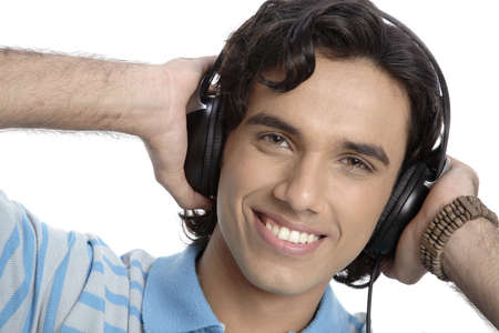 Teenage boy listening to music on headphones and smiling