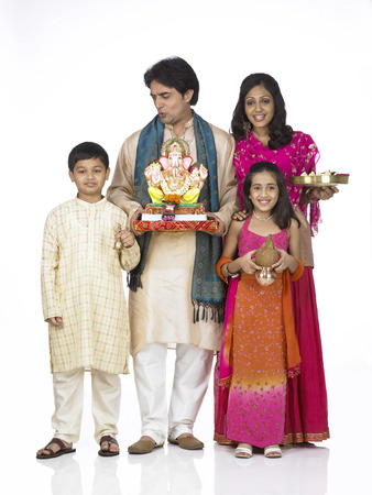South Asian Indian family with father mother son and daughter holding statue of lord Ganesha and Kalash Aarti thali