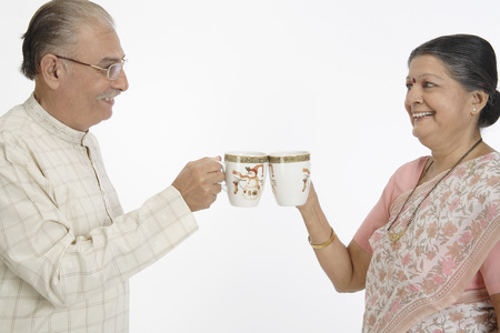 Old happy couple holding tea or coffee mugs touching each other in their hand saying cheers and smiling