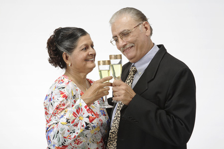 Old couple,old man and woman holding champagne glasses tossing for cheers