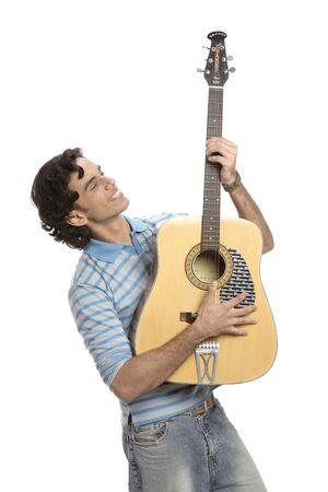 Teenage boy playing musical string instrument guitar Stock Photo