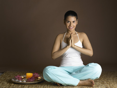 South Asian Indian woman praying with prayer utensil and smiling Imagens