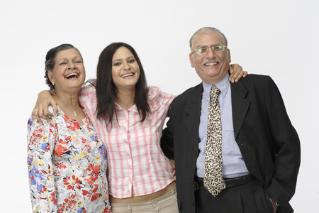 Young girl standing between old couple and laughing Stock Photo